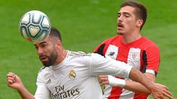Bek Real Madrid, Daniel Carvajal, duel udara dengan pemain Athletic Bilbao, Inigo Cordoba, pada laga La liga di Stadion San Mames, Minggu (5/7/2020). Real Madrid menang 1-0 atas Athletic Bilbao. (AFP/Ander Gillenea)