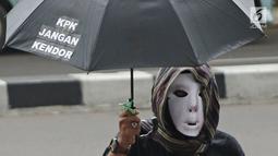 Seorang demonstran menggunakan topeng dan payung saat berunjuk rasa di depan Gedung KPK, Jakarta, Jumat (9/3). Demonstran mendesak KPK menahan Gubernur Jambi Zumi Zola karena sudah ditetapkan sebagai tersangka suap. (Liputan6.com/Herman Zakharia)