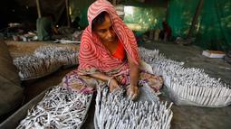 """Pekerja mengisi tabung dengan gulungan kertas berisi bubuk mesiu untuk petasan, di sebuah pabrik pinggiran Ahmadabad, Senin (22/10). Permintaan petasan di India semakin meningkat jelang perayaan Festival """"Cahaya"""" Diwali bagi umat Hindu. (AP/Ajit Solanki)"""