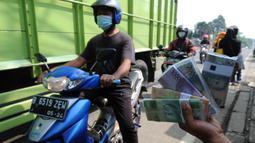 Penjual jasa penukaran uang menawarkan uang baru di kawasan Jalan Raya Parung, Bogor, Jawa Barat, Jumat  (7/5/2021). Penjual jasa penukaran uang memungut tambahan biaya sebesar 5 sampai 10 persen dari jumlah uang yang ditukarkan. (merdeka.com/Arie Basuki)