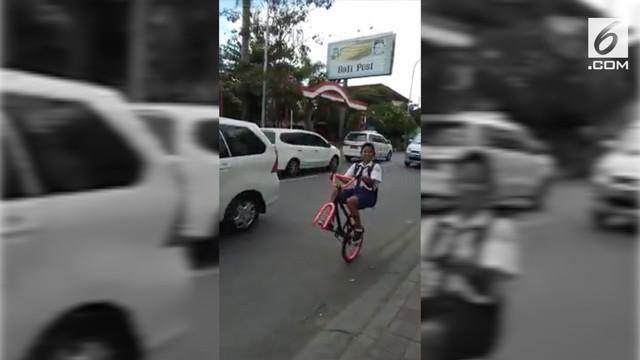 Siswa SMP Bali melakukan atraksi unik. Yaitu bersepeda tanpa roda depan