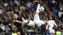 Pemain Real Madrid, Cristiano Ronaldo (kanan) melakukan tendangan salto melewaati pemain Malmo FF, Anton Tinnerholm  pada lanjutan Liga Champions Grup A di Stadion Satiago Bernabeu, Rabu (9/12/2015) dini hari WIB. (AFP Photo/ Pierre-Philippe Marcou)