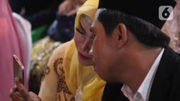 Pasangan peserta nikah massal jelang pelaksanaan itsbat nikah di halaman Balai Kota DKI Jakarta, Selasa (31/12/2019). 633 pasangan, terdiri dari pernikahan baru 143 pasangan dan 490 pasangan itsbat nikah mengikuti acara nikah massal yang digelar Pemprov DKI Jakarta. (Liputan6.com/Helmi Fithriansyah)