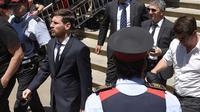 Lionel Messi berjalan dengan santai usai mengikuti sidang kasus pajak yang dituduhkan kepadanya bersama Jorge Messi di Kantor Pengadilan Barcelona, (2/6/2016). (AFP/Lluis Gene)