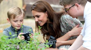 Duchess of Cambridge Kate Middleton melihat hasil foto seorang anak saat ikut serta belajar fotografi dengan Action for Children di Kingston upon Thames, Inggris (25/6/2019). (AFP Photo/Chris Jackson)