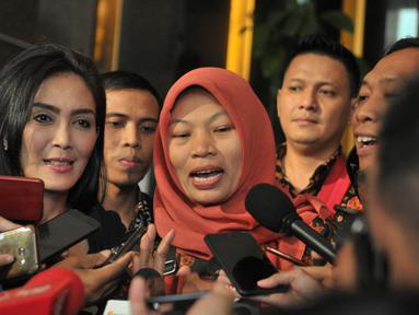 Terpidana kasus pelanggaran ITE Baiq Nuril Maknun (tengah) didampingi politikus PDIP Rieke Diah Pitaloka memberi keterangan saat tiba di Kantor Kemenkumham, Jakarta, Senin (8/7/2019). Baiq Nuril datang untuk menemui Menkumham Yasonna Laoly guna membahas pemberian amnesti. (merdeka.com/Iqbal Nugroho)