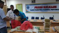 Personel BNN Riau dengan barang bukti 30 kilogram sabu yang disita dari kurir bermobil mewah. (Liputan6.com/M Syukur)