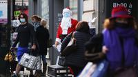 Warga berjalan melewati seseorang yang berpakaian Sinterklas di luar sebuah pasar swalayan di Paris, Prancis, 25 November 2020. Kebijakan karantina wilayah (lockdown) virus corona COVID-19 secara nasional dapat dicabut pada 15 Desember jika kondisi kesehatan di negara itu membaik. (Xinhua/Gao Jing)