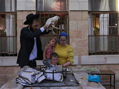 Seorang pria Yahudi ultraortodoks mengayunkan seekor ayam di atas kepala anggota keluarganya saat melakukan ritual Kapparot di Yerusalem, 13 September 2021. Kapparot adalah ritual transfer dosa ke ayam yang dilakukan sebelum Yom Kippur (Hari Penebusan). (MENAHEM KAHANA/AFP)