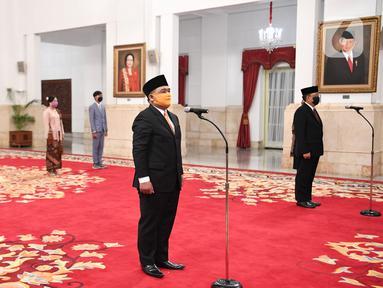 Kepala Badan Pelindungan Pekerja Migran Indonesia (BP2MI) Benny Rhamdani (kiri) dan Komisioner KPU I Dewa Kade Wiarsa Raka Sandi mengikuti pelantikan di Istana Negara, Jakarta, Rabu (15/4/2020). (Antarafoto/Hafidz Mubarak/Pool)