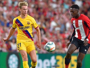 Striker Athletic Bilbao, Inaki Williams (kanan) membawa bola dari kejaran gelandang Barcelona, Frenkie de Jong  selama pertandingan perdana La Liga Spanyol di Stadion San Mames, Sabtu (17/8/2019). Bilbao menang tipis atas Barcelona dengan skor 1-0. (AFP Photo/Ander Gillenea)