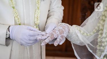 Pengantin pria memasangkan cincin ke pasangannya usai akad nikah di KUA Jagakarsa, Jakarta, Sabtu (6/6/2020). Pada masa penerapan PSBB transisi, pihak KUA tersebut menikahkan sebanyak delapan hingga 10 pasangan pengantin per hari. (Liputan6.com/Faizal Fanani)