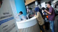 Calon penumpang kapal penyeberangan eksekutif mengantre membeli tiket di Pelabuhan Eksekutif Sosoro, Merak, Banten, Minggu (2/6/2019). Tarif naik kapal penyeberangan eksekutif sebesar Rp 50.000 untuk dewasa dan Rp 34.000 untuk anak-anak. (Liputan6.com/Helmi Fithriansyah)