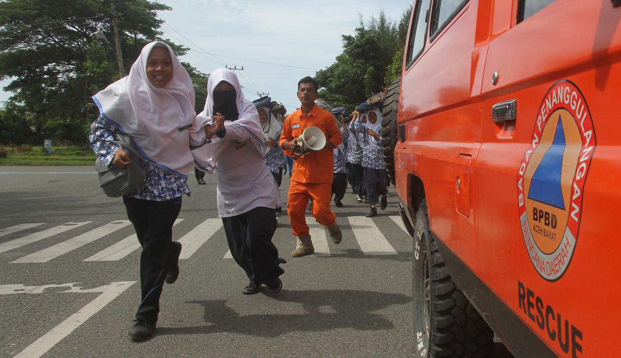 Sejumlah murid berlari saat berpartisipasi dalam latihan tsunami di Meulaboh, Aceh, (5/9). Latihan ini menyimulasikan gempa berkekuatan 9,3 di lepas pantai barat pulau Sumatra di Indonesia. (AFP Photo/Januar)