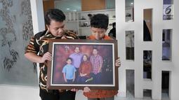 Muhammad Ivanka Rizaldi Nugroho (kiri) dan Muhammad Aufa Wikantyasa Nugroho (kanan) anak dari Kepala Pusat Data Informasi dan Humas BNPB Sutopo Purwo Nugroho melihat  foto keluarga di rumah duka Raffles Hils, Cimanggis,  Depok, Jawa Barat, Minggu (7/7/2019). (Liputan6.com/Herman Zakharia)