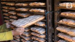 Pekerja tengah menata oncom di industri rumahan untuk di jual di wilayah Jakarta, Selasa (19/11/2019). Uncom yang di jual seharga Rp 2000 untuk memenuhi kebutuhan di pasar pasar tradisional di kawasan tersebut. (Liputan6.com/Angga Yuniar)