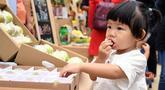 Seorang gadis kecil mencicipi produk-produk pertanian pada acara perayaan untuk menandai festival panen petani China di Distrik Pinggu, Beijing, ibu kota China, pada 24 September 2020. (Xinhua/Ren Chao)