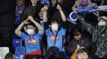 Dua suporter Napoli mengenakan masker menunggu dimulainya pertandingan antara Napoli dan Barcelona di Stadion San Paolo di Naples, Italia, Selasa, (25/2/2020). Italia melaporkan kenaikan kasus infeksi virus Corona COVID- 91 menjadi lebih 272 kasus. (AP Photo/Andrew Medichini)