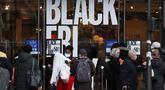 """Sejumlah orang berjalan melewati poster """"Black Friday"""" di Paris, Prancis, pada 4 Desember 2020. Sempat ditunda selama sepekan akibat karantina wilayah (lockdown) nasional, pesta belanja tahunan """"Black Friday"""" di Prancis akhirnya dimulai pada Jumat (4/12). (Xinhua/Gao Jing)"""