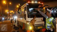 Petugas memberhentikan bus kota karena menaikan penumpang diatap bus saat malam takbiran di kawasan Matraman, Jakarta Timur, Jum'at (17/7/2015) malam. Tindakan tersebut dapat membahayakan keselamatan penumpang dan orang lain.(Liputan6.com/Faisal R Syam)