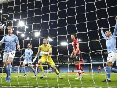 Pemain Manchester City Kevin De Bruyne (kiri) mencetak gol ke gawang Southampton pada pertandingan Liga Inggris di Etihad Stadium, Manchester, Inggris, Rabu (10/3/2021). Manchester City makin kokoh berada di puncak klasemen Liga Inggris usai mengalahkan Southampton 5-2. (Clive Brunskill/Pool via AP)
