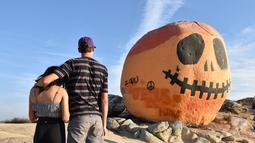 Orang-orang mengunjungi Pumpkin Rock (Batu Labu) di puncak sebuah bukit di Norco,  California, AS (18/10/2020). Menjelang perayaan Halloween, Pumpkin Rock, sebongkah batu raksasa yang dilukisi seperti Jack-O'-Lantern besar, menjadi objek wisata yang populer bagi pengunjung. (Xinhua/Gao Shan)