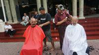 Wali Kota Solo, FX Hadi Rudyatmo dan Wakil Wali Kota Solo, Achmad Purnomo ikuti aksi tolak bala corona dengan cukur gundul, Rabu (25/3).(Liputan6.com/Fajar Abrori)