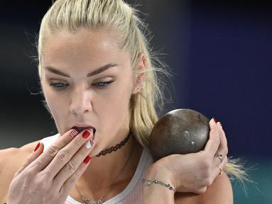 Ivona Dadic membasahkan jarinya yang dihiasi dengan cat kuku saat perlombaan tolak peluru putri dalam Kejuaraan Atletik Indoor Eropa 2021 di Torun. (Foto: AFP/Andrej Isakovic)