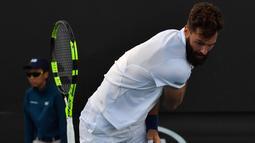 Petenis Prancis Benoit Paire melempar raketnya saat pertandingan putaran pertama melawan petenis Spanyol Guillermo Garcia-Lopez pada hari kedua turnamen tenis Australia Terbuka di Melbourne (16/1). (AFP Photo/Paul Crock)