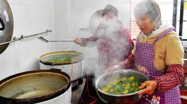 Sukarelawan memasak di sebuah kantin untuk warga lanjut usia (lansia) di Desa Yingshan, Kota Quanzhou, Provinsi Fujian, China pada 17 Desember 2020. Banyak desa dan komunitas di Quanzhou mendirikan kantin makanan gratis untuk warga berusia 60 tahun ke atas yang tinggal sendiri. (Xinhua/Wei Peiquan)