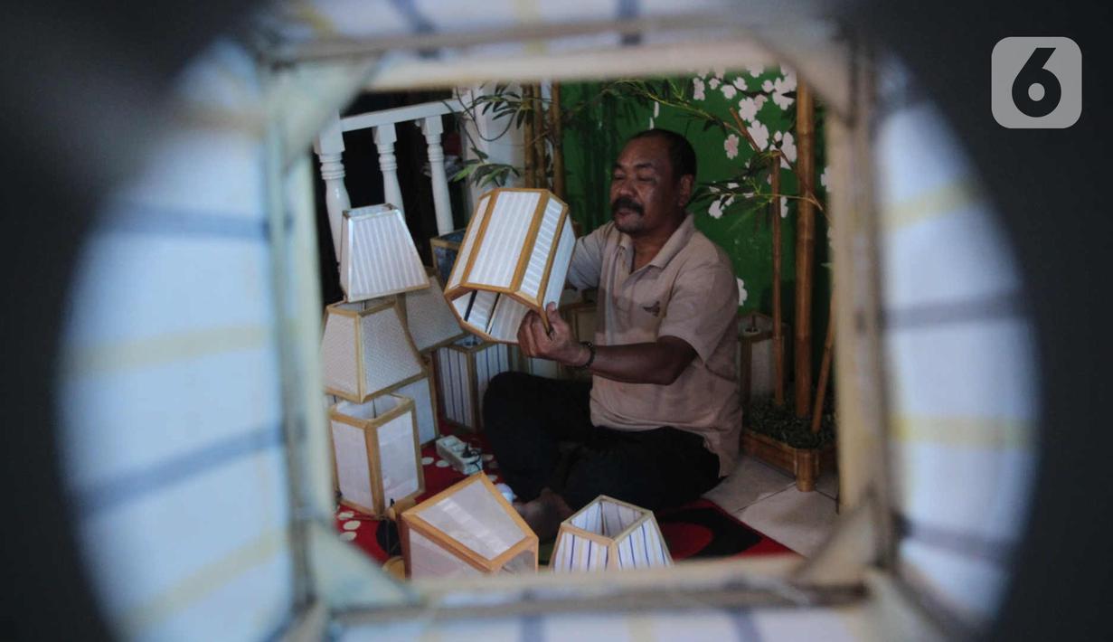 Nana Suryana (52), perajin lampion hias, mengerjakan pesanan konsumen di kawasan Benda, Kota Tangerang. Selasa (9/3/2021). Lampion hasil karyanya dibanderol dengan harga bervariasi mulai dari Rp 50ribu hingga Rp 1 juta. (Liputan6.com/Angga Yuniar)