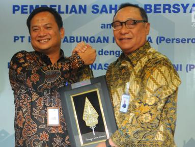 Dirut PT Bank Tabungan Negara (Persero) Tbk. Maryono (kanan) berjabat tangan dengan Dirut PT Permodalan Nasional Madani (Persero) (PNM) Arief Mulyadi usai penandatanganan perjanjian pembelian saham bersyarat PNMIM dari PNM di Kementerian BUMN, Jakarta, Senin (22/4). (Liputan6.com/Angga Yuniar)