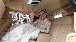 Aktris Olga Lydia berada di dalam mobil seusai menjalankan sakramen pernikahan di Gereja Katedral, Jakarta, Jumat (21/4). Aktris Olga Lydia dan Aris Utama menjalankan sakramen pernikahan. (Liputan6.com/Herman Zakharia)