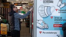 Seorang pria membeli produk dari mesin penjual otomatis yang menjual masker, sarung tangan, dan cairan pembersih tangan di Warsawa, Polandia, Sabtu (11/4/2020). Mulai 16 April, warga di Polandia diwajibkan untuk mengenakan masker saat berada di tempat umum. (Xinhua/Zhou Nan)
