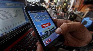 """Seorang warga mencoba memainkan game """"Bersihkan Wakil Rakyat"""" di kawasan Pasar Baru, Jakarta, (7/10/14). (Liputan6.com/Faizal Fanani)"""