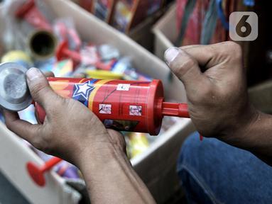 Pedagang memainkan salah satu terompet berbahan plastik yang dijualnya di kawasan Pasar Gembrong, Jakarta, Minggu (29/12/2019). Berbeda pada tahun sebelumnya, penjualan terompet plastik jelang perayaan malam Tahun Baru 2020 lebih marak dibandingkan terompet kertas. (merdeka.com/Iqbal Nugroho)