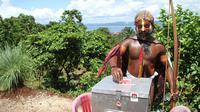 Setelah menggunakan hak pilihnya, pria ini pun tampak memasukkan kertas ke dalam kotak suara. (AFP PHOTO / Liva Lazore)