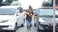 Petugas menyemprotkan disinfektan ke kendaraan warga di salah satu pos cek poin Kota Malang untuk mencegah penyebaran Corona Covid-19 (Humas Pemkot Malang)
