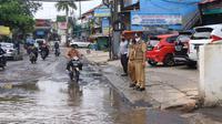 Jalan rusak yang terus tergenang air di Bintara Raya, Bekasi. (Liputan6.com/Bam Sinulingga)