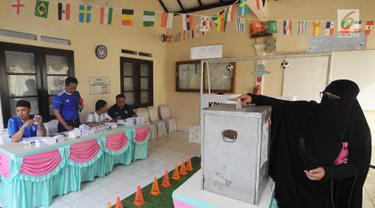 Warga menggunakan hak pilihnya pada pelaksanaan Pilkada Serentak 2018 di TPS 31 Mutiara Sentul, Bogor, Rabu (27/6). TPS ini didekorasi dengan konsep piala dunia untuk menarik minat pemilih agar hadir dalam pencoblosan. (Merdeka.com/Arie Basuki)