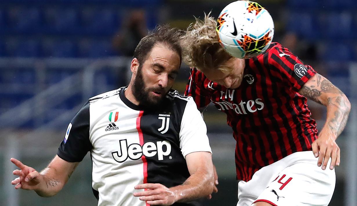 Bek AC Milan, Simon Kjaer melompat saat berebut bola dengan penyerang Juventus, Gonzalo Higuain dalam laga giornata 31 Serie A 2019-2020 di San Siro, Rabu (8/7/2020) dini hari WIB. AC Milan sukses kalahkan Juventus 4-2.  (AP Photo/Antonio Calanni)