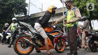 Petugas Kepolisian melakukan razia pengendara motor dengan knalpot bising di kawasan Monumen Nasional (Monas), Jakarta, Minggu (7/3/2021). Razia knalpot bising tersebut guna memberikan kenyamanan bagi warga yang hendak berolahraga di area tersebut. (Liputan6.com/Herman Zakharia)