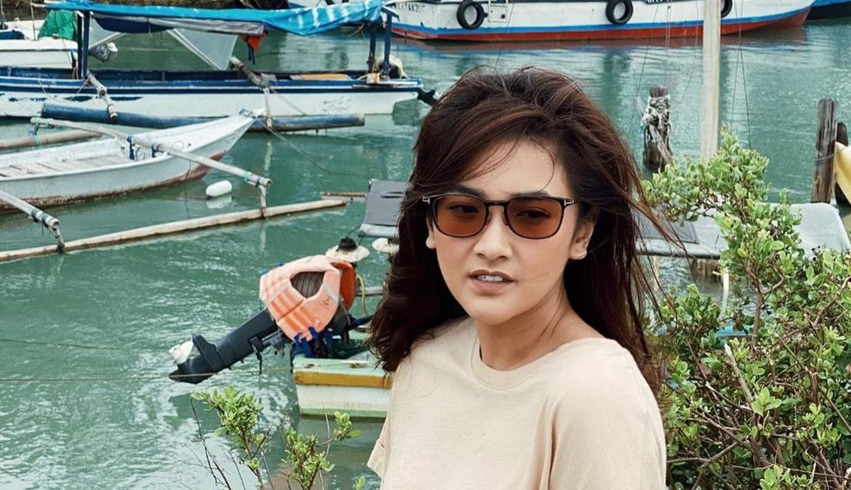 Pemilik nama lengkap Nadya Arina Pramudita memang memiliki hobi traveling. Gayanya saat traveling pun sangat simpel namun tetap keren. Seperti saat ia tampil dengan mengenakan kaus dan kacamata cokelat saat berada di pinggir laut. (Liputan6.com/IG/@nadyaarina)