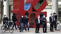 Pejalan kaki menunggu untuk menyeberang jalan di kawasan bisnis Shinjuku, Tokyo, Jepang, 17 April 2020. Banyak warga Jepang tidak mengindahkan imbauan untuk tetap di rumah setelah pemerintah mengumumkan darurat nasional akibat virus corona COVID-19. (AP Photo/Eugene Hoshiko)