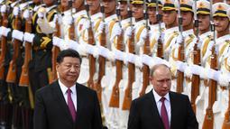 Presiden Rusia Vladimir Putin didampingi Presiden China Xi berjalan bersama saat upacara penyambutan di Aula Besar Rakyat di Beijing, China (8/6). Xi menambahkan, kedua negara juga saling mendukung kepentingan masing-masing. (AFP/Pool/ Greg Baker)