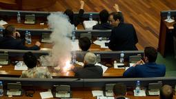 Seorang anggota parlemen Partai Vatevendosje menyalakan tabung gas air mata dalam sesi sidang di Pristina, Kosovo, Rabu (21/3). Aksi dilakukan demi mencegah pemungutan suara terkait masalah kesepatakan perbatasan dengan Montenegro (AP Photo/Visar Kryeziu)