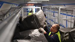 Seorang pekerja memasukkan paket ke kereta peluru Fuxing di Stasiun Kereta Barat Beijing di Beijing, ibu kota China (1/11/2020). Otoritas perkeretaapian China meluncurkan layanan khusus pada Minggu (1/11), yang akan berlangsung hingga 20 November. (Xinhua/Zhang Chenlin)