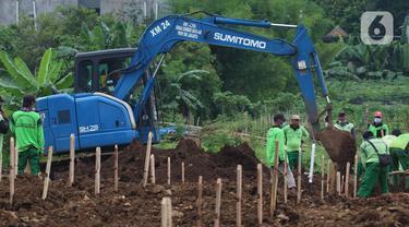 Aktivitas alat berat jenis eksavator membantu proses penggalian makam jenazah dengan protokol COVID-19 di area khusus TPU Srengseng Sawah, Jakarta, Kamis (14/1/2021). Pada Selasa (12/1) lalu, 47 jenazah dimakamkan dengan protokol COVID-19 di TPU Srengseng Sawah. (Liputan6.com/Helmi Fithriansyah)
