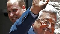 Presiden Palestina, Mahmud Abbas melambaikan tangan ketika menerima kedatangan Pangeran William dari Inggris di Tepi Barat Kota Ramallah, (27/6). Sebelumnya Pangeran Willian melakukan pertemuan dengan PM Israel. (AFP PHOTO / Ahmad Gharabli)