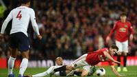 Gelandang Manchester United, Daniel James, dijatuhkan gelandang Liverpool, Fabinho, pada laga Premier League di Stadion Old Trafford, Manchester, Minggu (20/10). Kedua klub bermain imbang 1-1. (AFP/Oli Scarff)